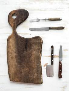 Kitchen ware set Old rustic chopping board made of walnut wood knives fork on a white background