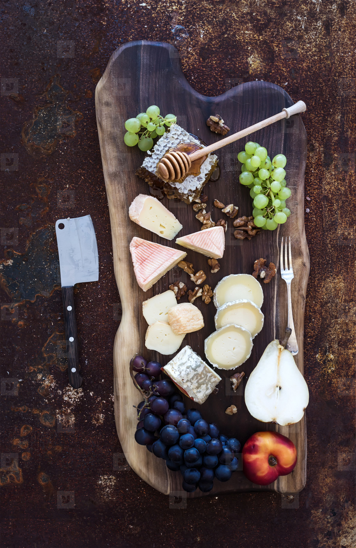 Wine appetizers set  French cheese selection  honeycomb  grapes  peach and walnuts on rustic wooden board over dark grunge metal background  Top view