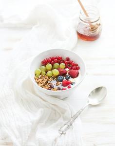 Healthy breakfast  Bowl of oat granola with yogurt  fresh berries and honey