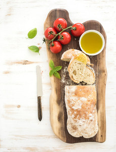 Freshly baked ciabatta bread with cherry tomatoes olive oil basil and salt on walnut wood board over white background top view