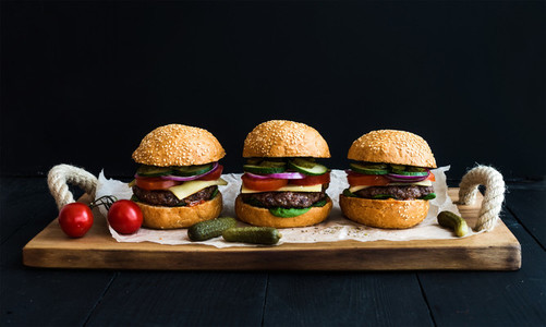 Fresh beef burgers on paper over rustic wooden tray  black background