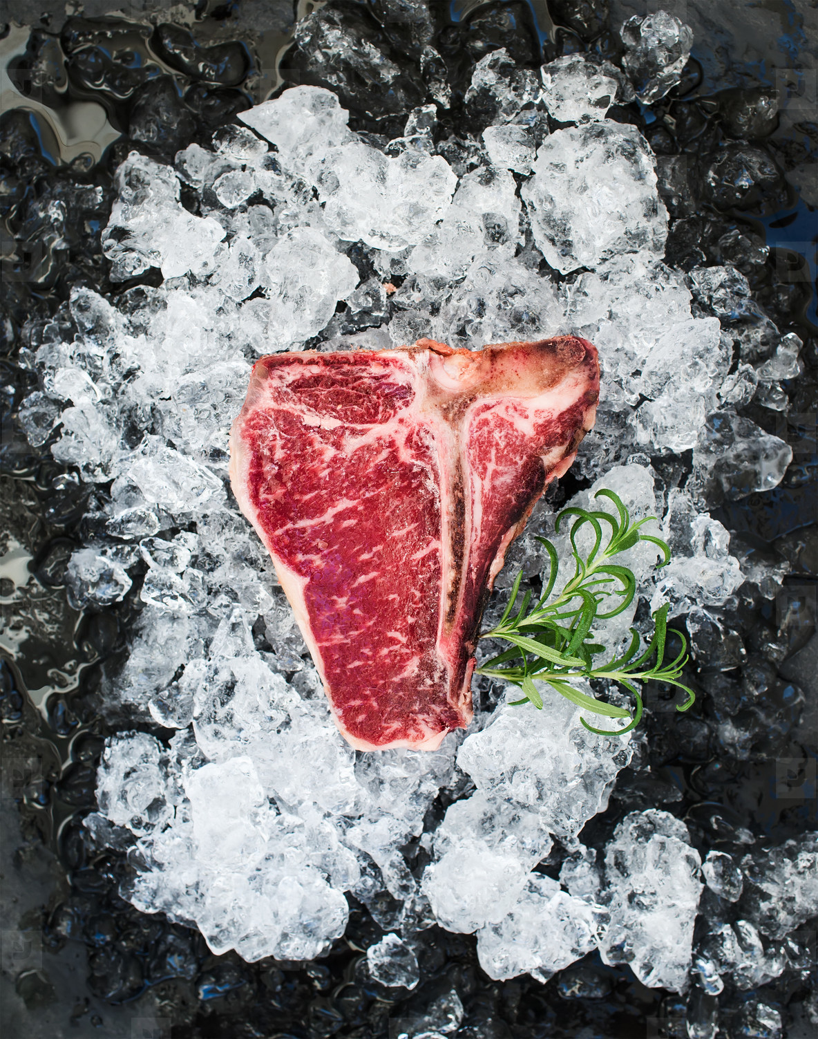 Raw fresh meat t bone steak on chipped ice with rosemary over dark slate stone backdrop
