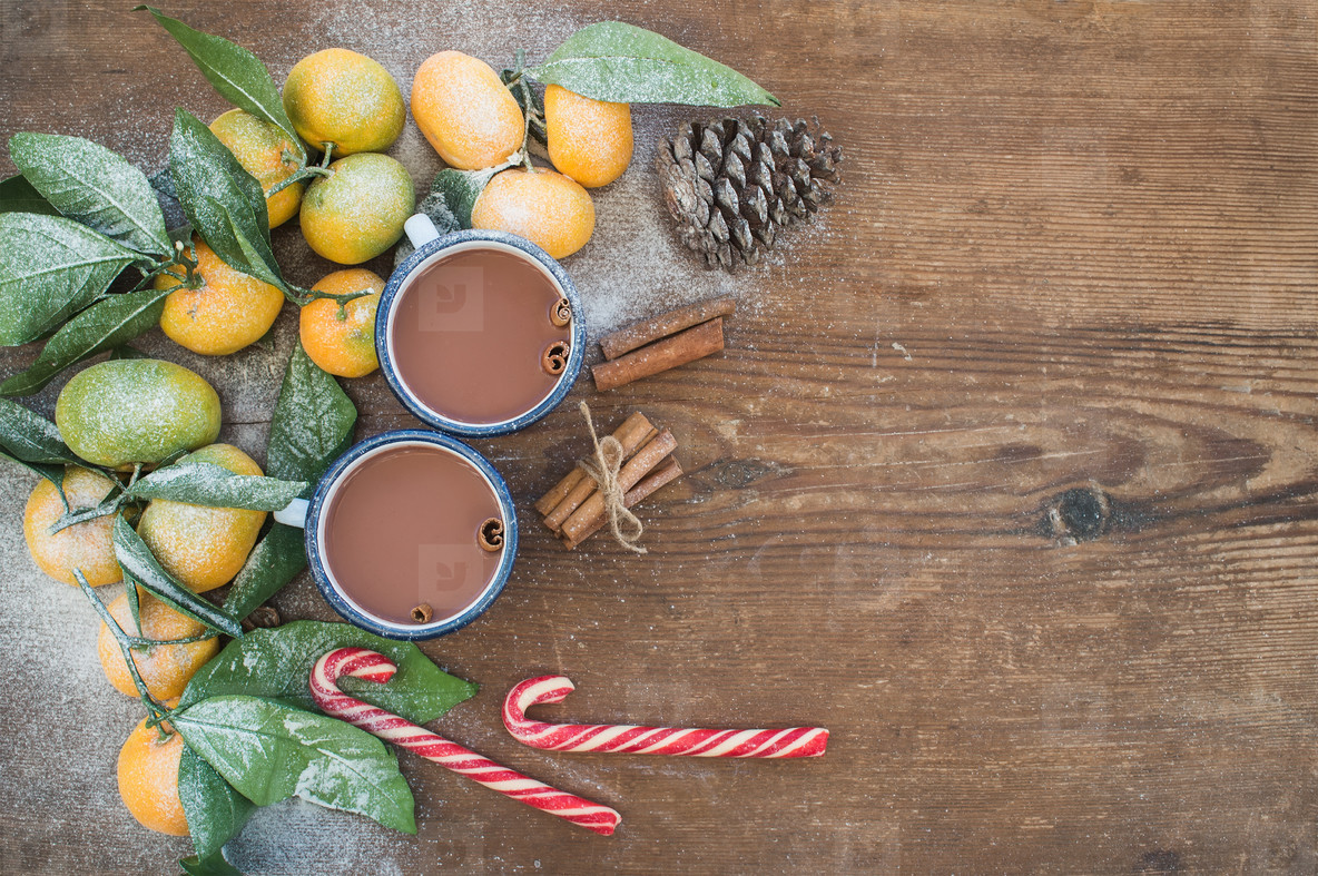Christmas or New Year frame  Fresh mandarins with leaves  cinnamon sticks  pine cone  hot chocolate in mugs and candy canes over rustic wooden background  top view