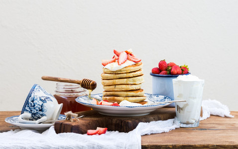 Breakfast set Pancake tower with fresh strawberries sour cream and honey on a porcelain plate over rustic wooden table Blue enamel cup full of berries behind white background