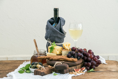 Glass of white wine  cheese board  grapes  fig  strawberries  honey and bread sticks  on rustic wooden table  light background
