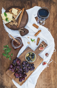 Glass of red wine  cheese board  grapes  walnuts  olives  honey and bread sticks on rustic wooden table