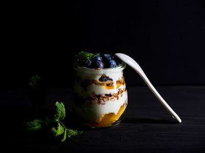 Yogurt oat granola with jam  blueberries and mint leavesin glass jar on black backdrop