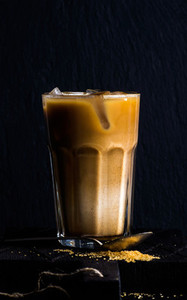 Iced coffee with milk in a tall glass  moka pot  black background