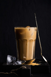 Iced coffee with milk in a tall glass black background