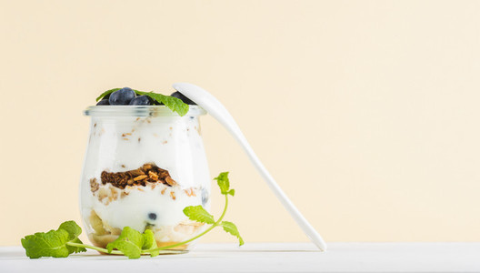 Yogurt oat granola with jam  blueberries and green leaves in glass jar on pastel yellow backdrop