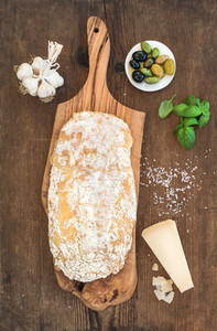 Freshly baked ciabatta bread with garlic  mediterranean olives  basil and Parmesan cheese on serving board over rustic wooden background