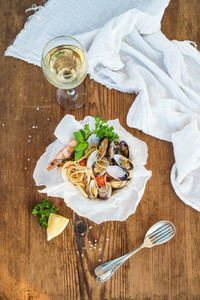 Seafood pasta  Spaghetti with clams and shrimps in bowl  glass of white wine over rustic wood background