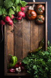 Fresh raw ingredients for healthy cooking or salad making  in rustic wooden tray over black background  top view  copy space  Diet  vegetarian food concept