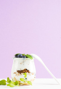 Yogurt oat granola with jam  blueberries and green leaves in glass jar on pastel lilac backdrop