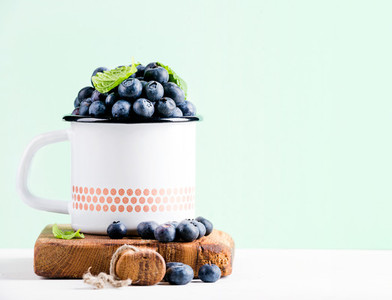 Fresh ripe blueberries in country style enamel mug on rustic wooden board over mint background