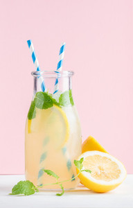 Bottle of homemade lemonade with mint ice lemons paper straws and pastel pink background