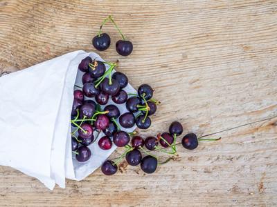 Paper bag of sweet cherries