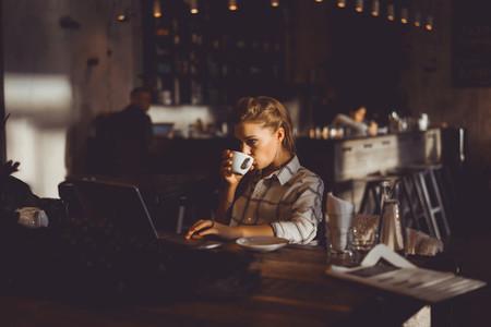 girl using laptop in cafe
