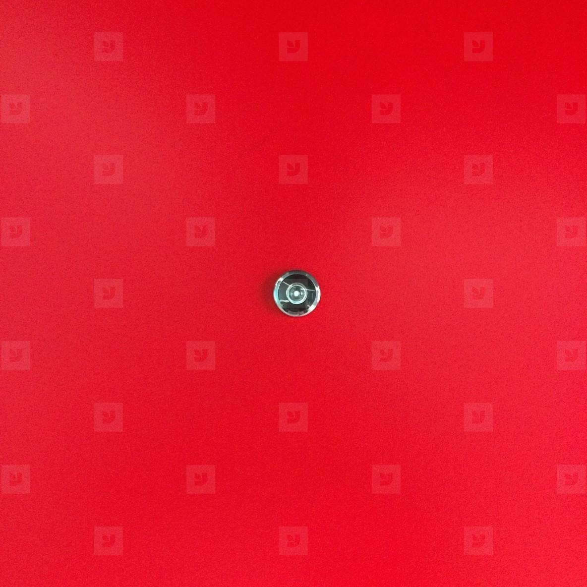 Door lens peephole on red wooden