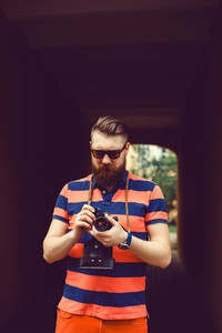 Beard man using film camera