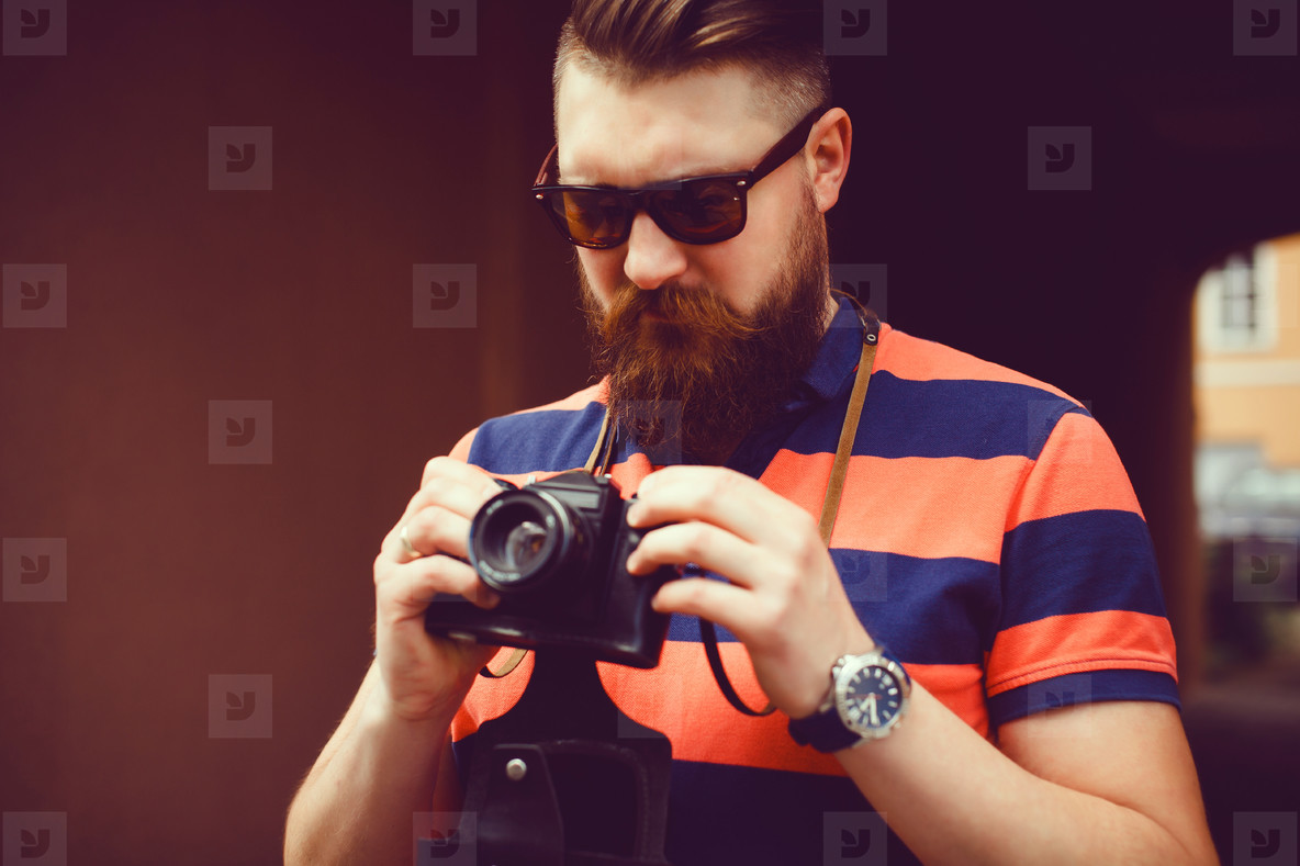 Beard man using film camera