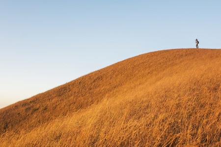 a man standing on a gold grass