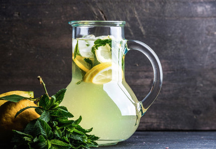 Homemade lemonade with mint  lemon slices and ice over dark background  copy space