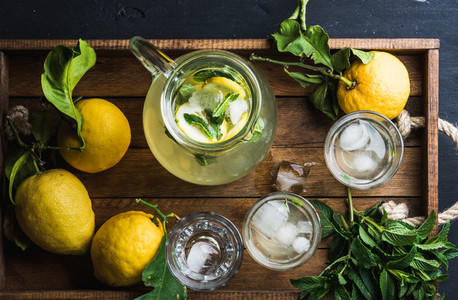 Jug and glasses with homemade lemonade  ice cubes on wooden tray  top view