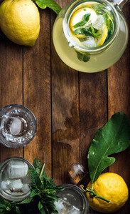 Jug with homemade lemonade  mint  fresh lemons and ice cubes on wooden background  top view  copy space