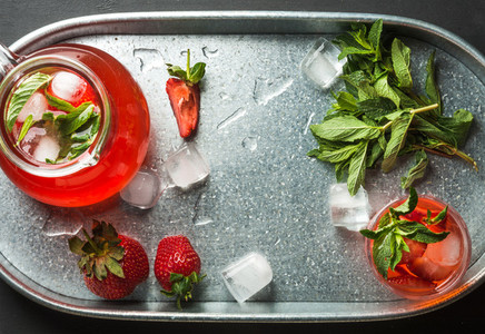 Homemade strawberry lemonade  mint and ice  served with fresh berries in metal tray  top view