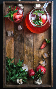 Homemade strawberry lemonade mint and ice served with fresh berries on rustic wooden tray over dark background top view copy space