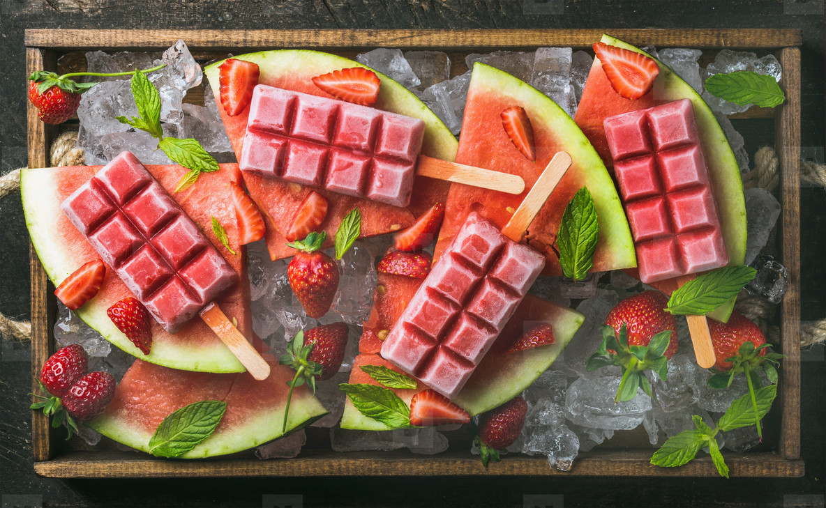Homemade watermelon strawberry popsicles in wooden tray
