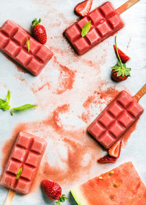 Strawberry watermelon ice cream popsicles with fresh mint leaves over steel tray background copy space