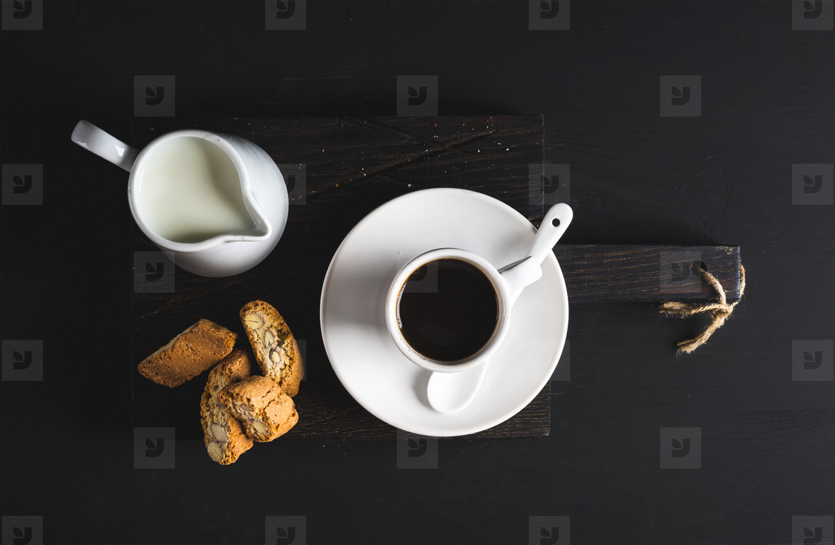 Cup of hot espresso  creamer with milk and cookies on dark rustic wooden board over black background