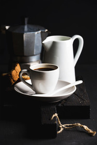 Italian coffee set for breakfast  Cup of hot espresso  creamer with milk  cantucci and moka pot on dark rustic wooden board over black background