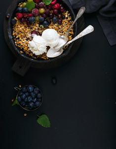 Healthy breakfast Oat granola crumble with fresh berries seeds ice cream and mint leaves in iron skillet pan on dark wooden board over black backdrop top view copy space