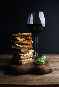 Caprese sandwich or panini and glass of red wine  Whole grain bread  mozzarella  dried tomatoes  basil  Dark background  vertical composition