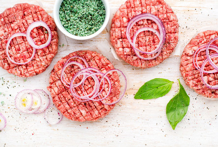 Raw ground beef meat cutlet for cooking burgers with onion rings and spices on white wooden background