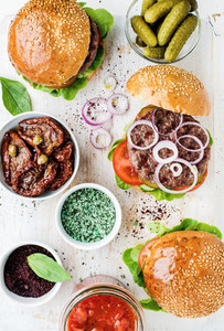 Homemade beef burgers with onion pickles vegetables sun dried tomatoes spices