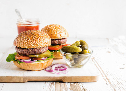 Two fresh homemade burgers pickles ketchup and onion rings on white wooden serving board