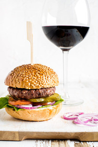 Fresh homemade burger on white wooden serving board with onion rings  glass of red wine