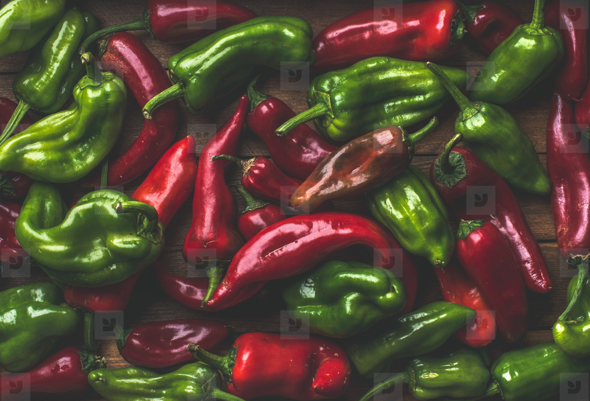 Background of colorful red and green bell peppers over wooden backdrop