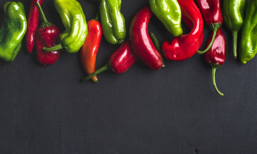 Colorful hot chili peppers on black wooden background copy space