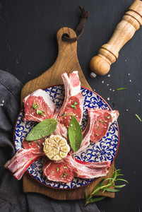 Raw uncooked lamb chops with herbs and spices on wooden board over dark  background