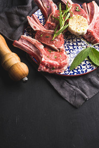 Raw uncooked lamb chops with herbs and spices on bright plate over dark wooden background copy space