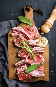 Raw uncooked lamb chops with herbs and spices on rustic wooden board over dark  background