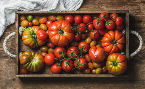 Colorful assortment of heirloom  bunch and cherry tomatoes in rustic tray over wooden background