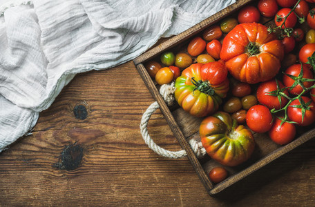 Colorful tomatoes of different sizes and kinds in dark wooden tray over rustic background  copy space