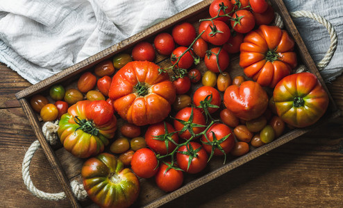 Colorful tomatoes of different sizes and kinds in dark wooden tray over rustic background
