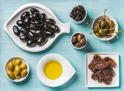 Mediterranean snack assortment  Black and green Greek olives  capers  olive oil  sun dried tomatoes over turquoise blue background